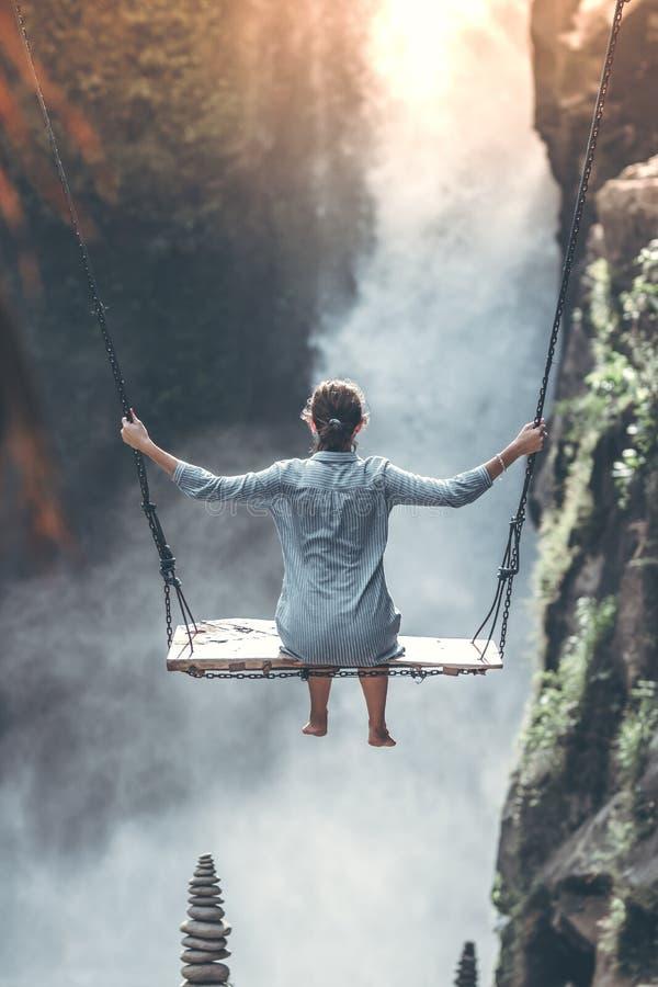 La bella donna oscilla vicino alla cascata nella giungla dell'isola di Bali, Indonesia immagine stock libera da diritti