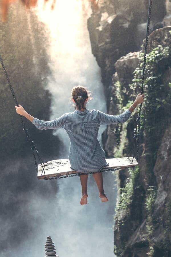 La bella donna oscilla vicino alla cascata nella giungla dell'isola di Bali, Indonesia fotografie stock libere da diritti