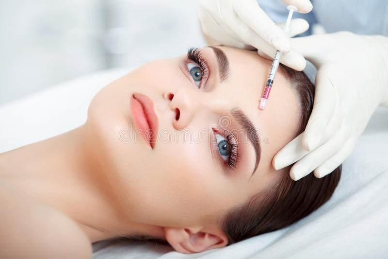 La bella donna ottiene l'iniezione nel suo fronte. Chirurgia estetica immagine stock libera da diritti