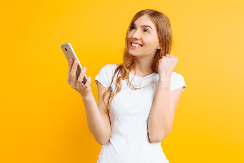 La bella donna pensierosa, utilizza un telefono cellulare, per messaggio, sguardi allo schermo di uno smartphone, su un fondo gia fotografia stock libera da diritti