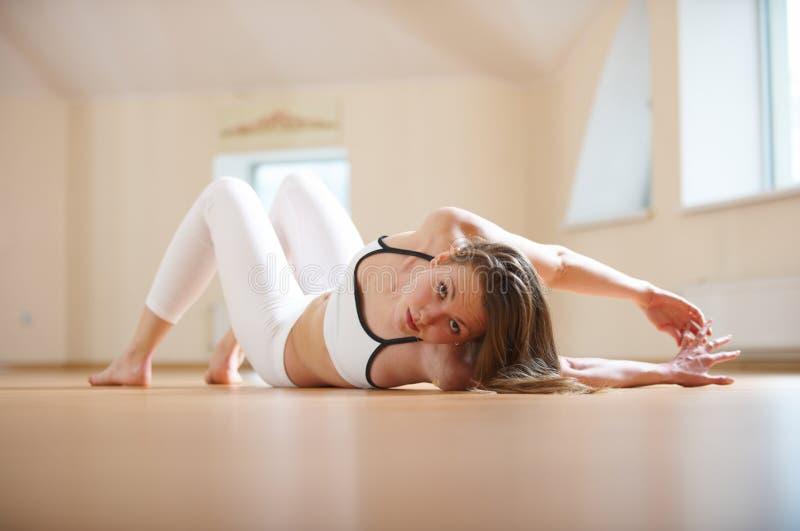 La bella donna pratica il asana torto di menzogne di yoga nello studio di yoga immagine stock