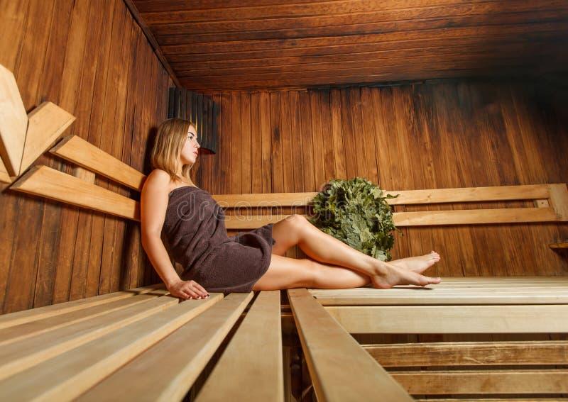 La bella donna prende il rilassamento nella sauna fotografia stock