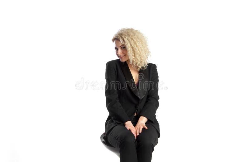 La bella donna riccia bionda si siede sulla sedia nell'affare nero Sui immagine stock