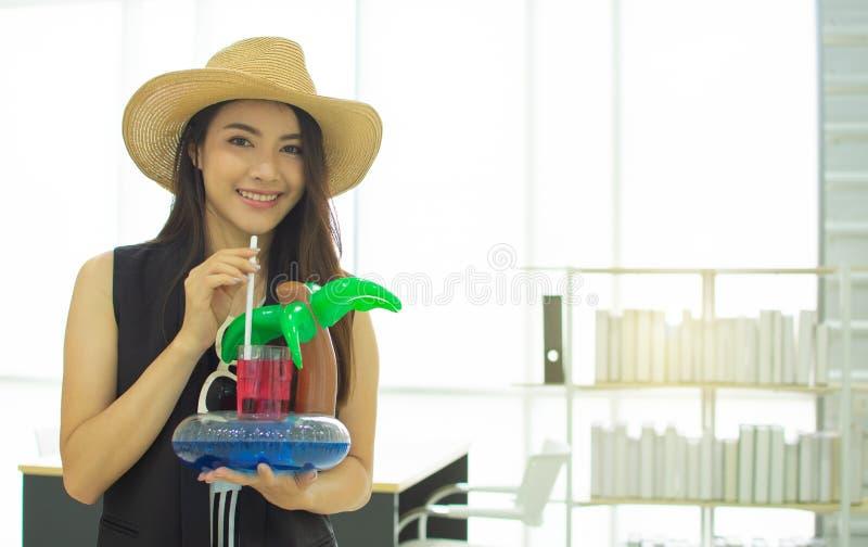 la bella donna 20s sta bevendo nell'ufficio immagine stock libera da diritti