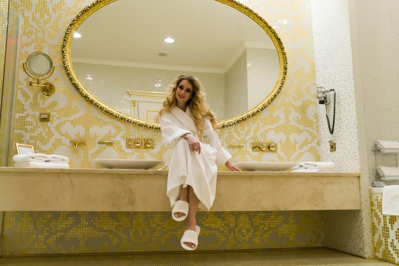 La bella donna seducente che flirta con la macchina fotografica sta sedendosi nel suo bagno Giovane donna di bellezza immagini stock