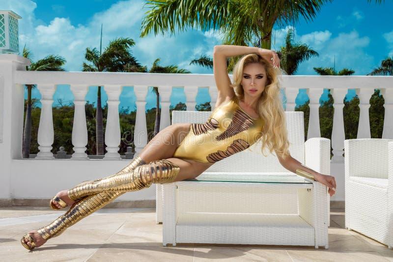 La bella donna sexy in bikini dell'oro ed oro calza la posa sull'albergo di lusso caraibico immagine stock