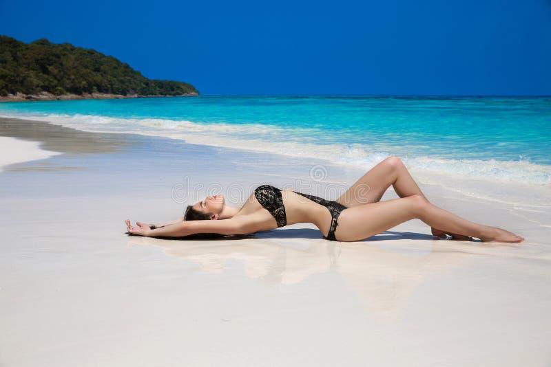 La bella donna sexy in bikini nero che si trova su tropicale esotico è immagine stock libera da diritti