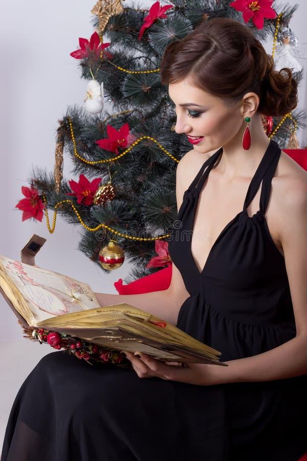 La bella donna sexy felice in vestito da sera con trucco e l'acconciatura si siede vicino ad un albero di Natale con un libro mag immagini stock