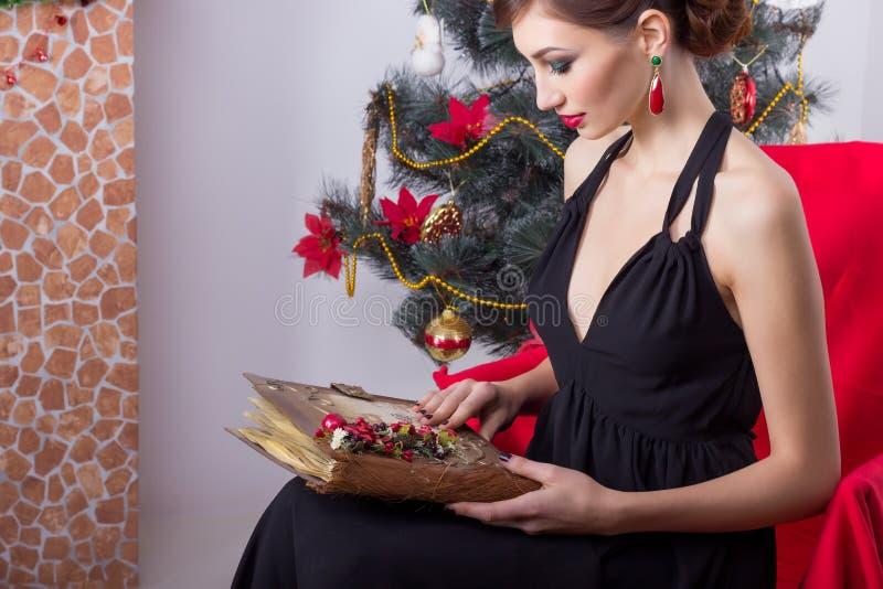 La bella donna sexy felice in vestito da sera con trucco e l'acconciatura si siede vicino ad un albero di Natale con un libro mag fotografie stock libere da diritti
