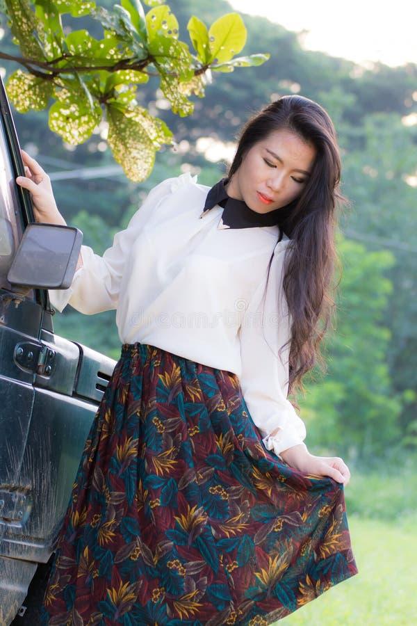 La bella donna si appoggia l'automobile, esaminante la macchina fotografica fotografia stock