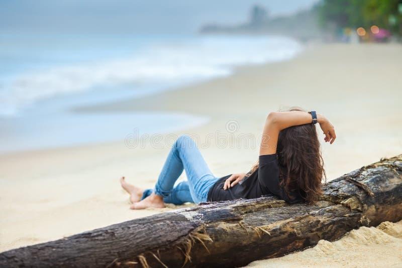 La bella donna si rilassa sulla spiaggia immagini stock