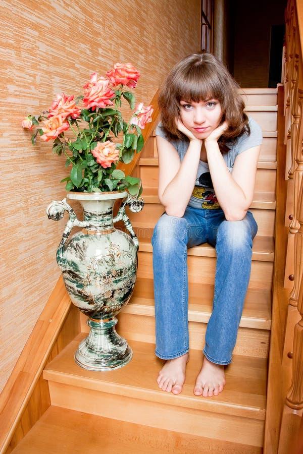 La bella donna si siede su una scala immagine stock