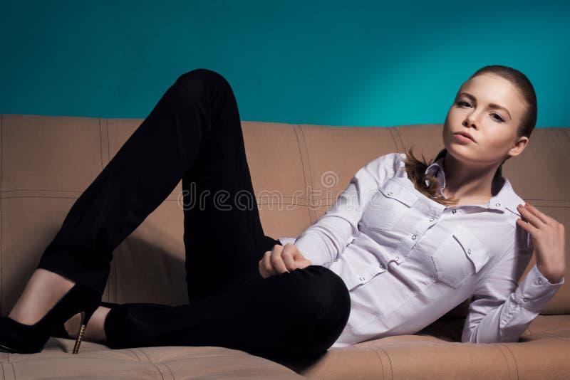 La bella donna si trova sullo strato e fuma una sigaretta fotografia stock
