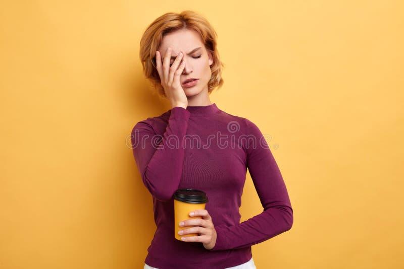 La bella donna sonnolenta stanca con una palma sul suo fronte porta il caffè immagine stock