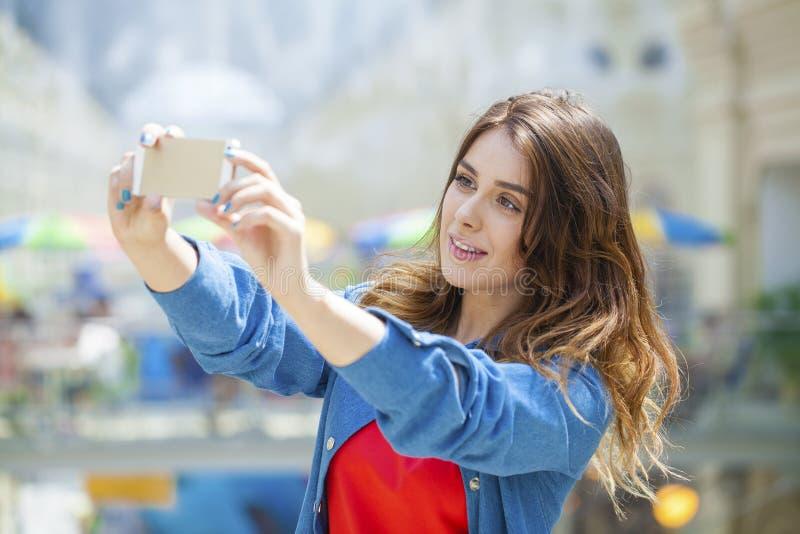La bella, donna sorridente prende un'immagine se stessa con uno smartp immagini stock