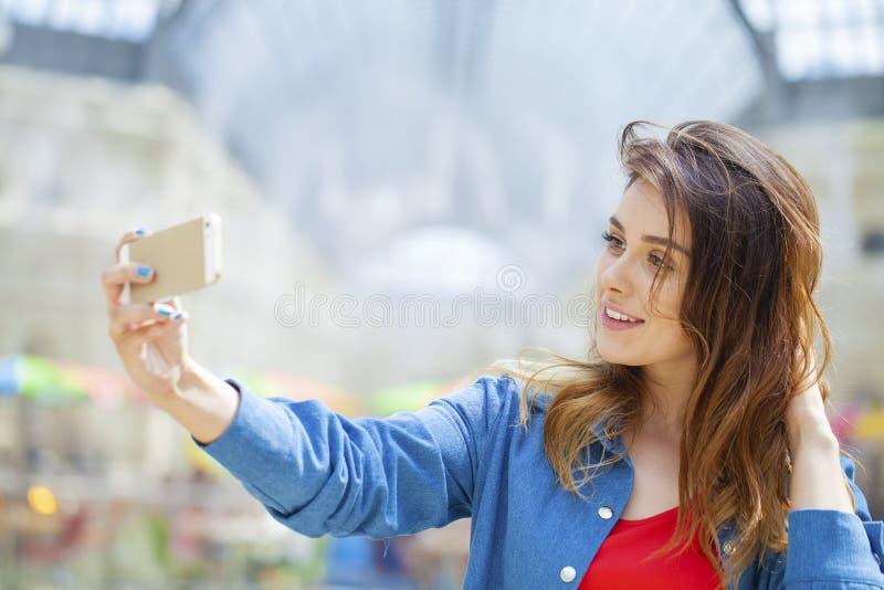 La bella, donna sorridente prende un'immagine se stessa con uno smartp immagine stock