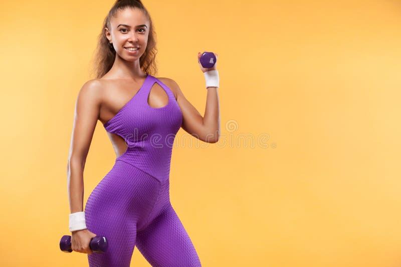 La bella donna sportiva con le teste di legno fa la forma fisica che si esercita al fondo bianco per restare adatta fotografia stock libera da diritti