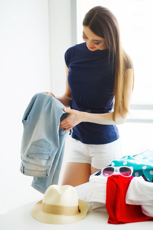 La bella donna sta imballando l'abbigliamento in valigia a casa fotografia stock libera da diritti