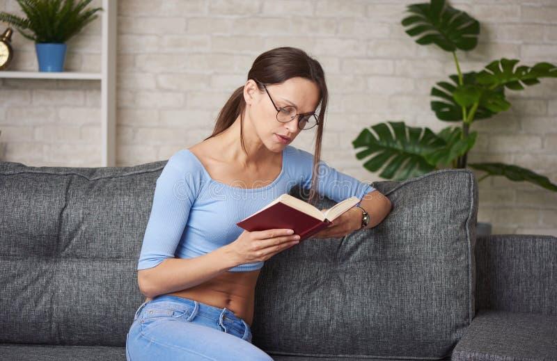 La bella donna sta leggendo un libro fotografia stock
