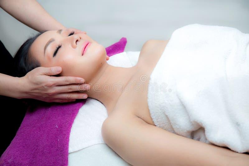 La bella donna sta ottenendo un massaggio facciale nel salone della stazione termale fotografia stock libera da diritti