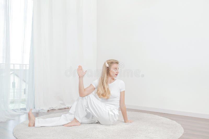 La bella donna sta praticando l'yoga a casa, facendo l'esercizio di Ardha Matsyendrasana, sedentesi in mezzo signore dei pesci po immagini stock libere da diritti