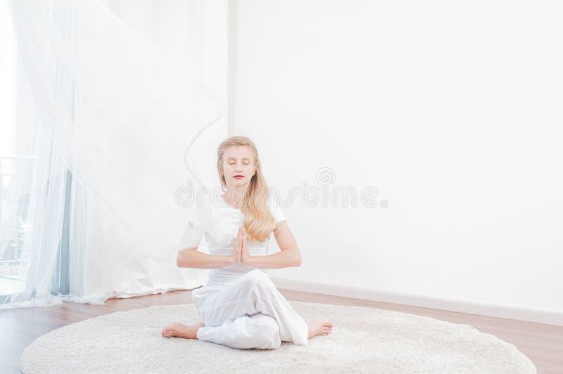 La bella donna sta praticando l'yoga a casa, ragazza che fa l'esercizio di Gomukasana, sedentesi nella posa del fronte della mucc immagini stock libere da diritti