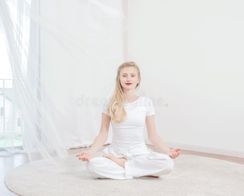 La bella donna sta praticando l'yoga a casa, ragazza che fa l'esercizio di Padmasana, sedentesi nella posa di Lotus immagini stock