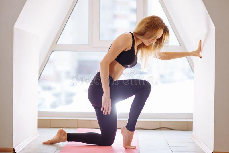 La bella donna sta preparando fare l'yoga alla classe di yoga fotografia stock libera da diritti
