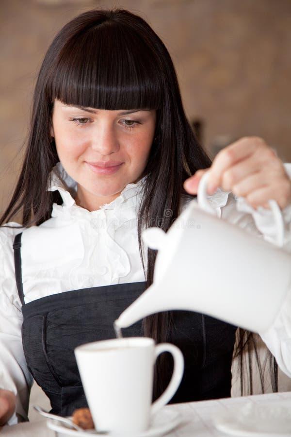 La bella donna sta preparando il tè fotografia stock libera da diritti