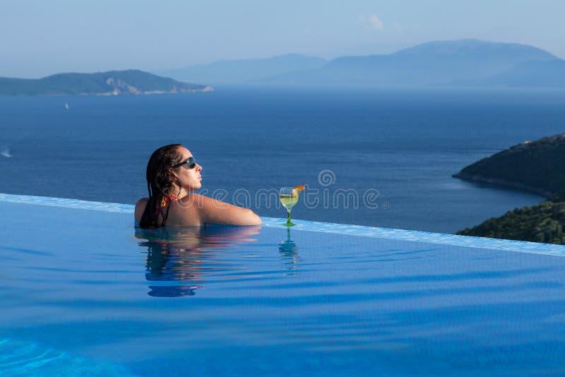 La bella donna sta rilassandosi in uno stagno dell'infinito immagine stock libera da diritti