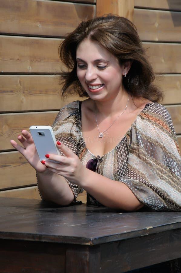 La bella donna sta utilizzando uno smartphone immagine stock