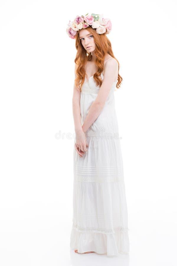 La bella donna tenera con capelli rossi lunghi in fiori si avvolge fotografia stock