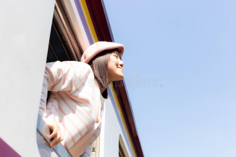 La bella donna turistica sta inalando l'aria fresca durante il treno che corre alla destinazione fotografia stock