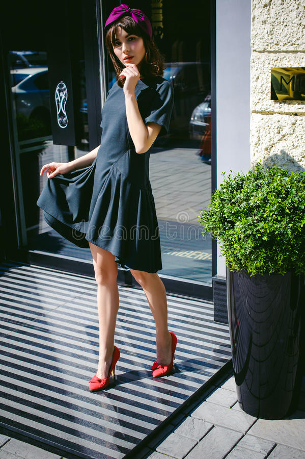 La bella donna in un vestito alla moda scuro passeggia avanti Ritratto di una ragazza alla moda immagine stock