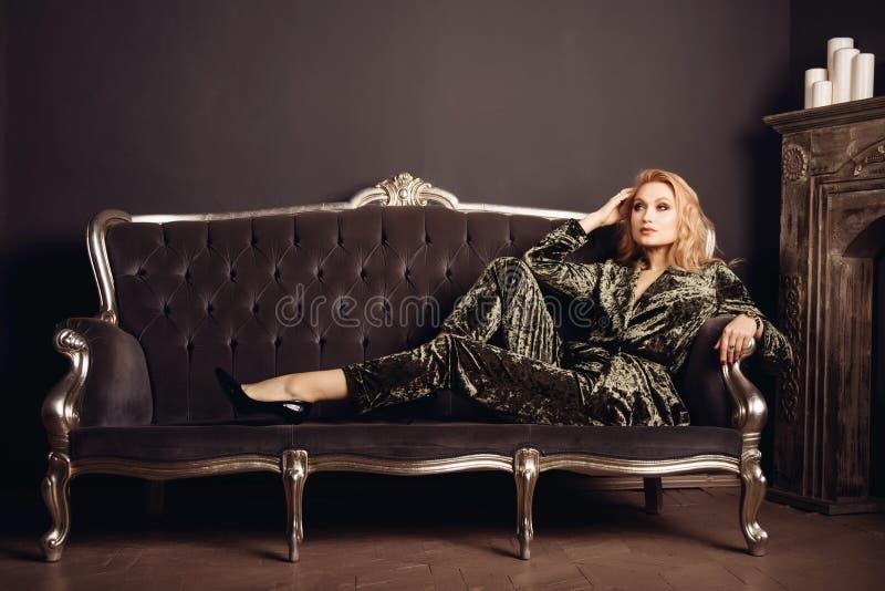 La bella donna in un vestito di velor si siede su uno strato d'annata vicino ad un camino con le candele fotografia stock libera da diritti