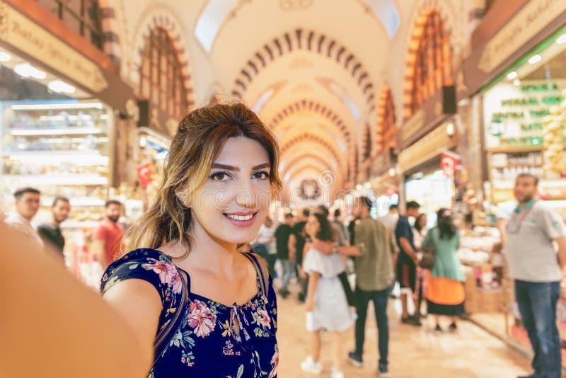 La bella donna in un vestito prende il selfie nel bazar dell'Egitto fotografia stock libera da diritti