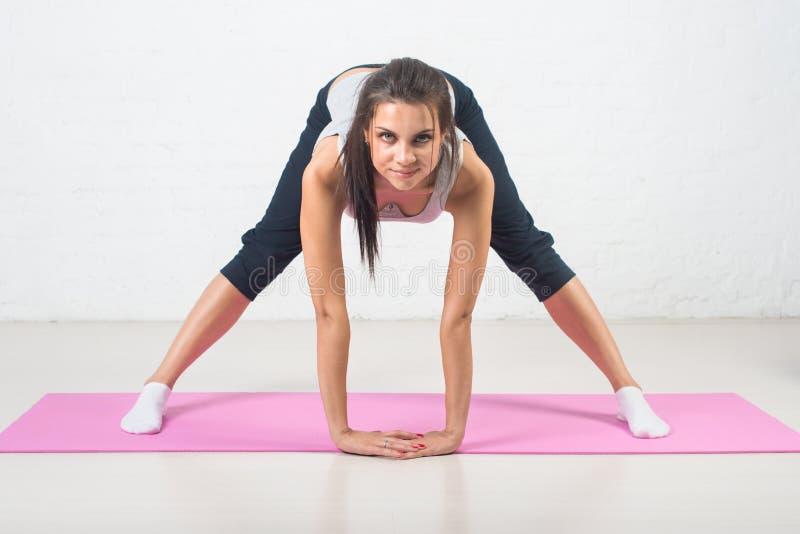 La bella donna va dentro per gli sport, forma fisica, facendo si esercita con un sorriso, allungante Stile di vita sano, salute fotografie stock libere da diritti
