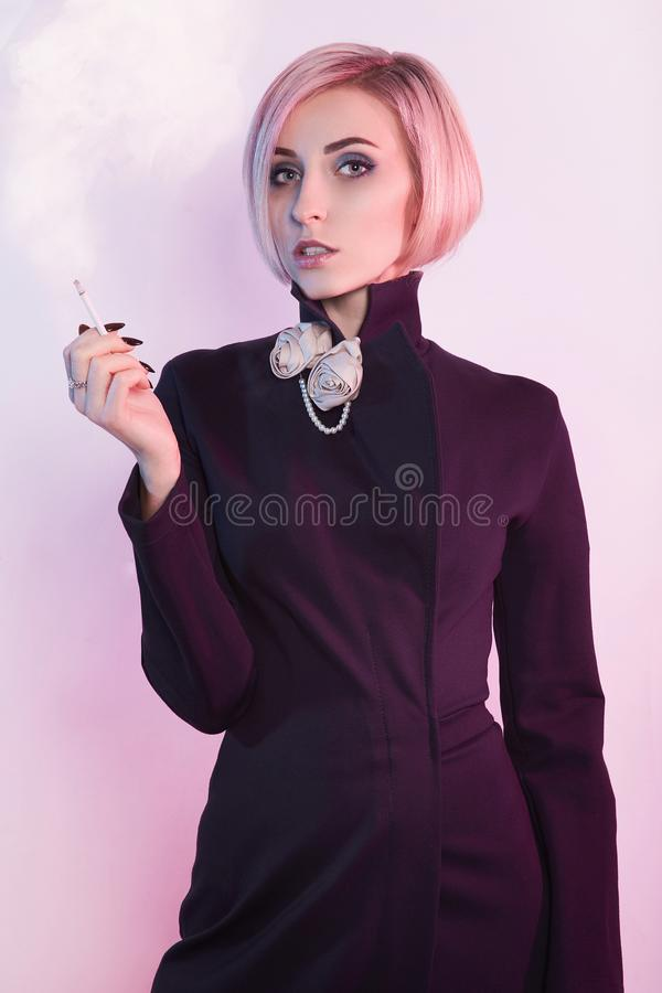 La bella donna in vestito, fuma una sigaretta fotografia stock libera da diritti