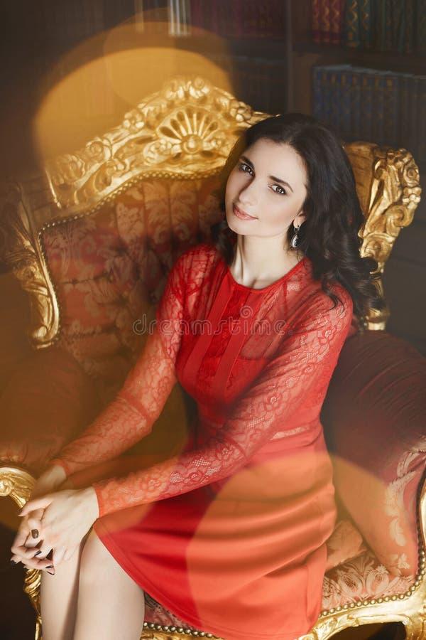 La bella e ragazza di modello castana affascinante con capelli ricci in vestito alla moda rosso si siede sulla poltrona d'annata  immagine stock