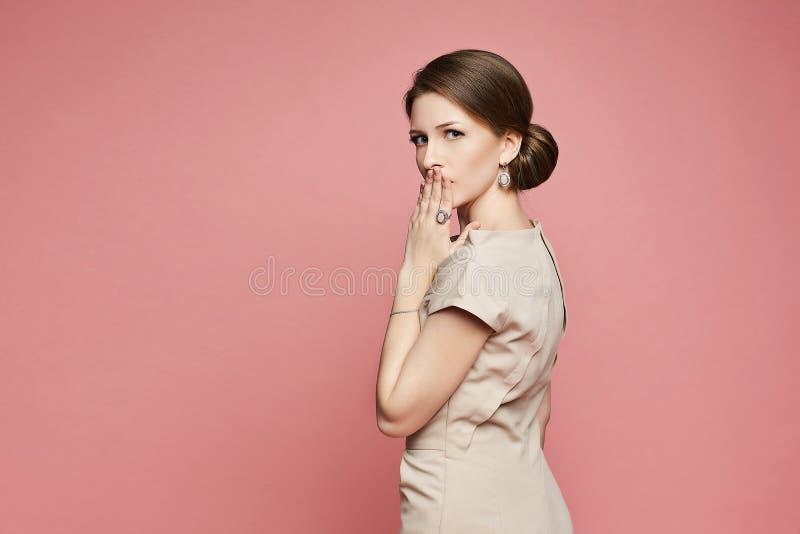 La bella e ragazza di modello castana alla moda sorpresa in vestito beige e con gli orecchini ha coperto la sua bocca di suoi man fotografia stock libera da diritti