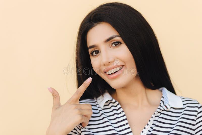La bella femmina con capelli scuri lussuosi, denti bianchi con i sostegni, indica alla bocca con il dito anteriore, annuncia i ga fotografia stock libera da diritti