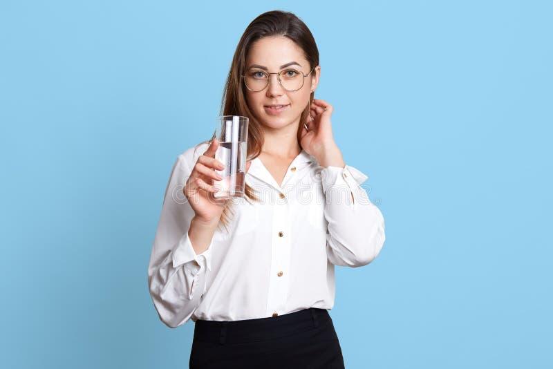 La bella femmina lavorante dura ha messo il mèche dei suoi capelli dietro l'orecchio, tiene il bicchiere d'acqua in sua mano Sign immagini stock libere da diritti