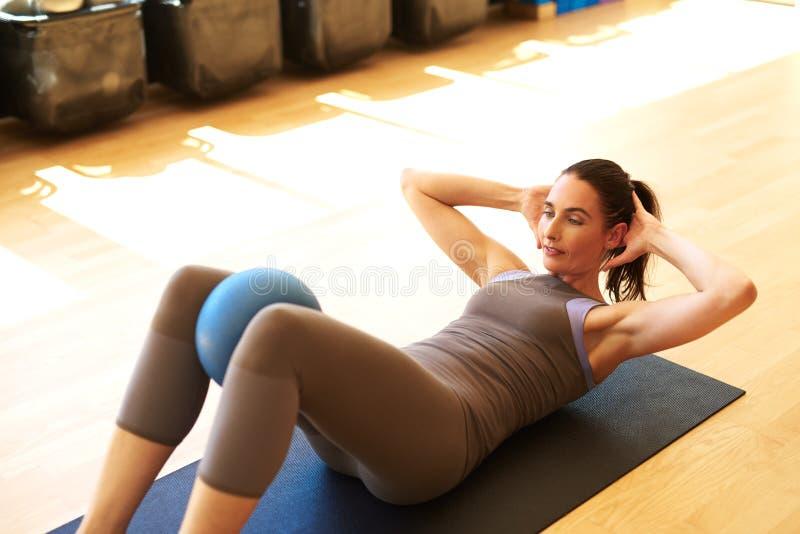 La bella femmina sta facendo i pilates fotografie stock