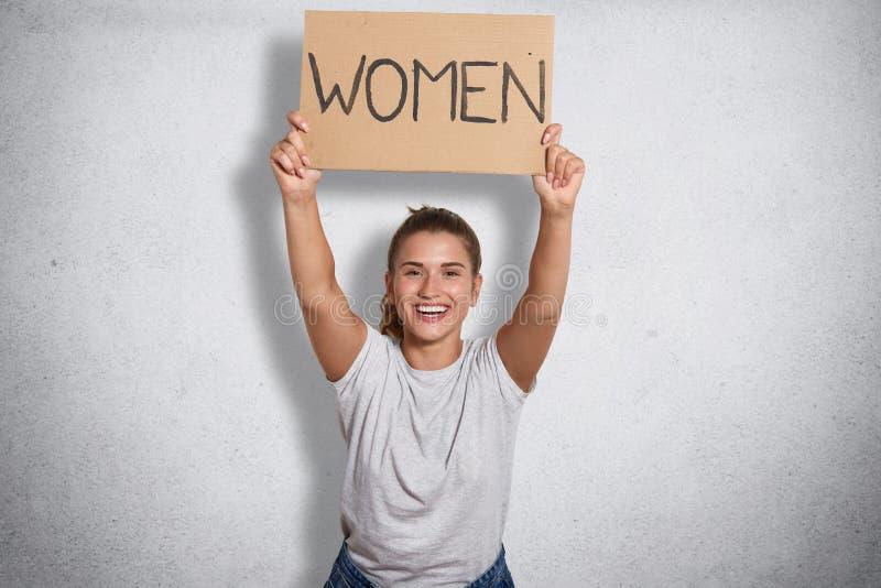 La bella femminista allegra che sorride francamente, alzando le donne dell'iscrizione in entrambe le mani, aspetta ad attività pu immagini stock