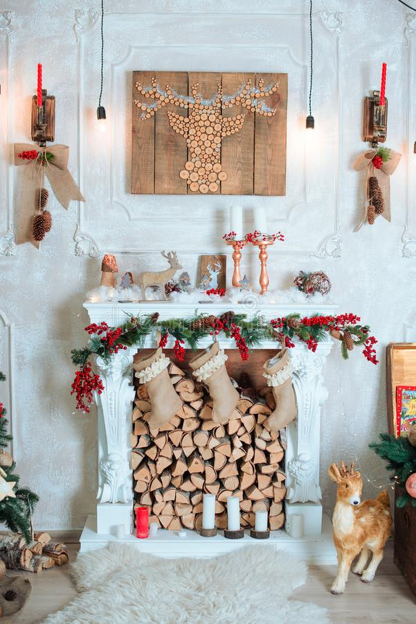 La bella festa ha decorato la stanza con l'albero di Natale, camino e con i presente Scena accogliente di inverno Interiore bianc fotografie stock