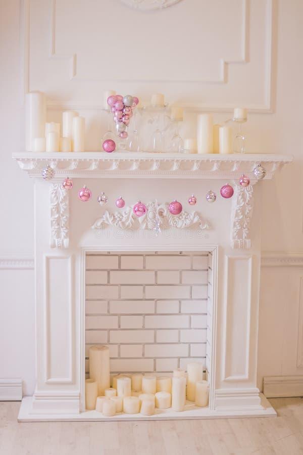 La bella festa ha decorato la stanza con l'albero di Natale, camino e con molte candele Scena accogliente di inverno Interiore bi fotografia stock libera da diritti