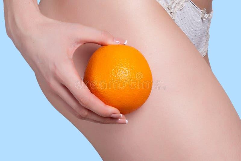 La bella figura femminile con un'arancia tiene vicino all'asino fotografia stock libera da diritti