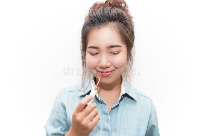 La bella fine della giovane donna osserva e facendo il trucco facendo uso di un labbro immagine stock