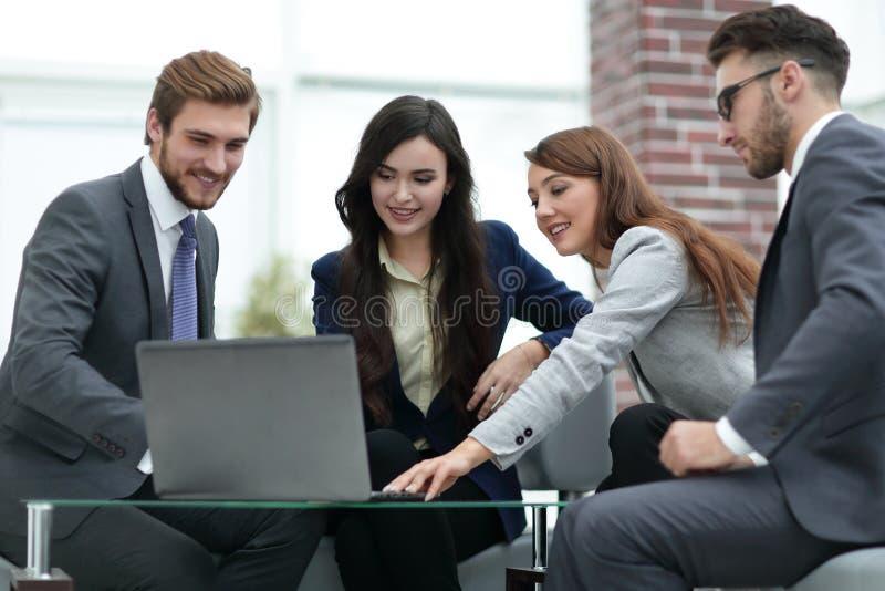 La bella gente di affari sta utilizzando un computer portatile durante il conferen immagine stock
