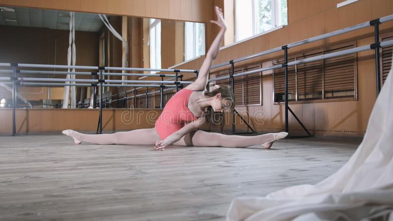 La bella ginnasta fa le spaccature in una stanza con il tornio e gli specchi di balletto fotografia stock